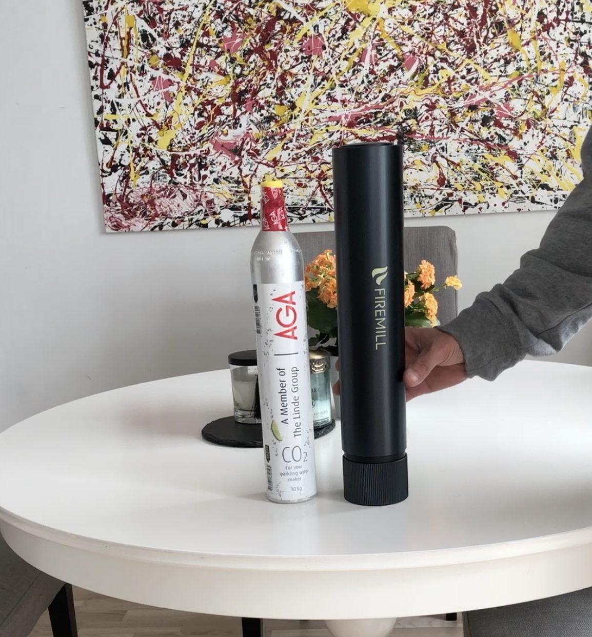 Svart Firemill och en kolsyreflaska på ett vitt runt bord